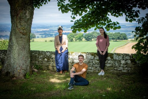 Three actors stand against a brick wall with Northumberland landscape behind